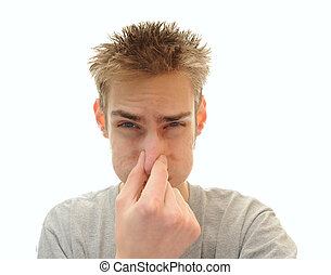 Man plugging his nose from odor - Young adult man tightly...