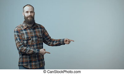Man pointing at copy space - Smiling bearded man pointing at...