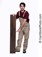 Man pointing at plank of laminate flooring