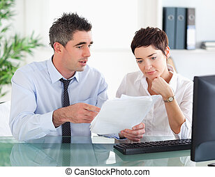 Man pointing at something to his colleague on a document