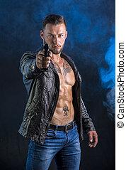 Man pointing gun to camera, wearing jacket on naked torso