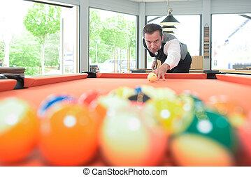 man poised to break at pool table