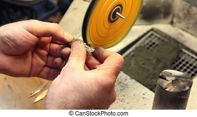 Man polishes jewelry on grinding wheel, closeup view