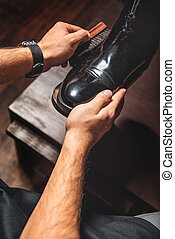 man polishing a leather pair of brogues - craftsman hands...