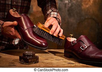 Man polishing leather shoes with brush. - Man polishing...