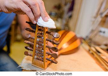 Man polishing pegs of banjo