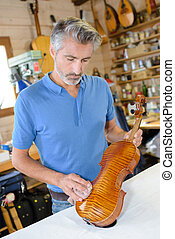Man polishing violin