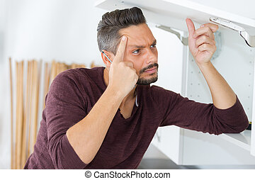 man pondering how to repair cupboard