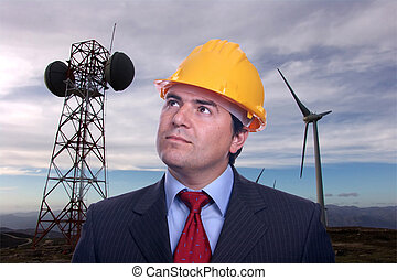 man portrait construction hat on Eolic energy turbines background