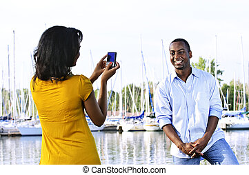 Man posing for picture near boats