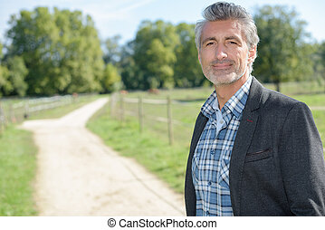 man posing in country lane