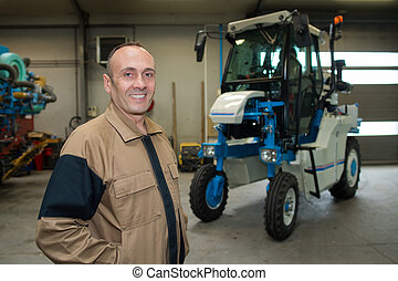 man posing next to a vehicular equipment