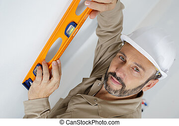man posing with a builders level