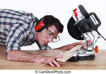 Man positioning a plank of wood in a mitre saw
