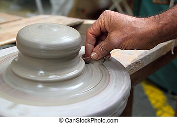 man potter hands working on pottery clay wheel