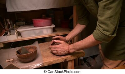Man potter kneading clay beats it for installation on a ...