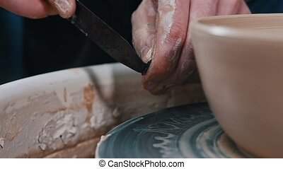 Man potter working with a pot of clay using a putty knife - ...
