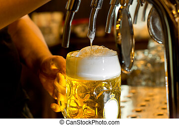 Man pouring a tankard of frothy beer - Close up of the hand...