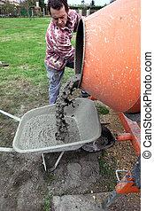 Man pouring cement into wheelbarrow