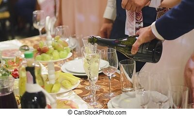 Man pouring champagne in a glass at the wedding party.