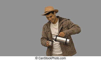 Man pouring coffee from a vacuum flask on grey screen in...
