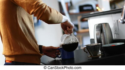 Man pouring coffee from glass jar into a coffee cup 4k - Man...