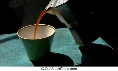 man pouring fresh hot coffee into the mug