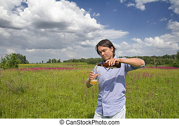 Man pouring himself a beer on a spring meadow