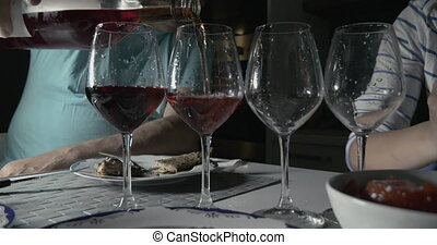 Man pouring red wine in four glasses.Unrecognizable