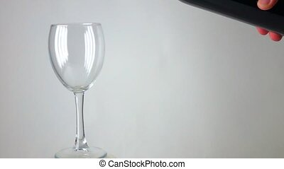 Man pouring red wine into a glass against gray background, super slow motion