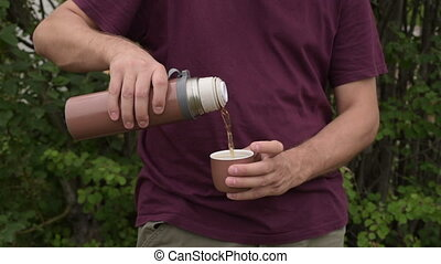 Man pouring tea from bottle into cup