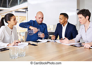 Meeting between four successful entrepreneurs taking place while one of them pours himself a glass of water as the other business people continue to discuss the relevant topics to be decided on.
