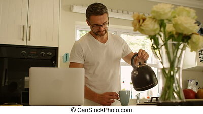 Man pouring water into coffee cup in kitchen 4k - Man...