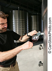 Man pouring wine from a steel vat