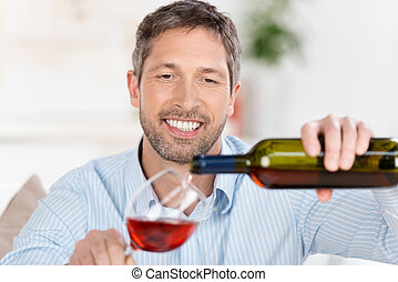 Man Pouring Wine In Wineglass At Home