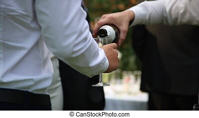 Man pouring wine into glasses at a party close-up