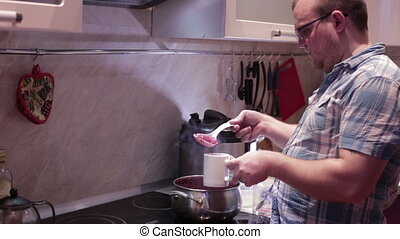 Man pours a ladle juice - Man pours into a white mug of...