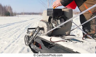 Man pours fuel into the gas tank of a mini snowmobile on a winter snowy road