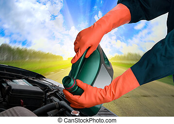 motor oil - man pours motor oil into the engine