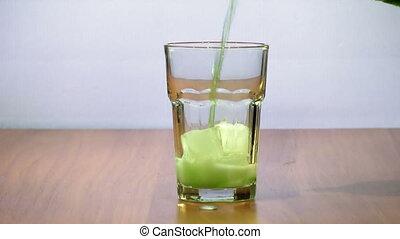 Man pours tarragon, estragon into a glass with ice. slowmotion