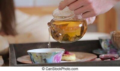 Man pours tea into a cup