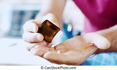 Man pours the pills out of the bottle on his hand . Medicine and health care concept.