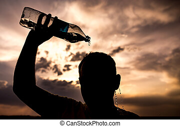 man pours water on his head in the sunset