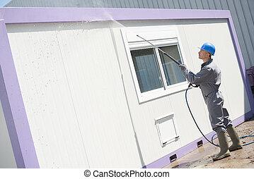 Man power washing building