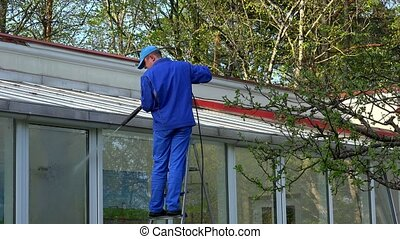 Man power washing conservatory roof and windows.