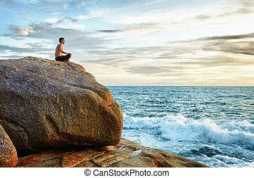 Man practices yoga on coast - meditation - A man practices...
