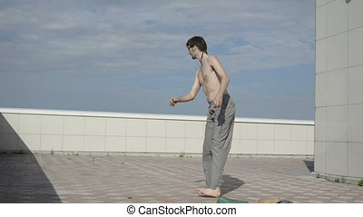 Man practices yoga on the roof