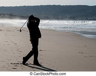 man practicing golf swing at beach