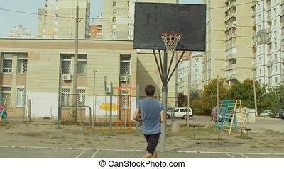 Man practicing layup shot on basketball court