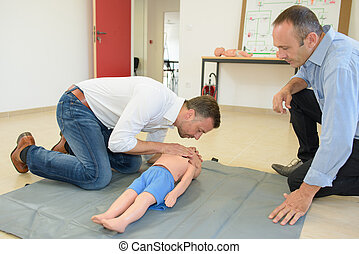 Man practicing resuscitation on a child dummy